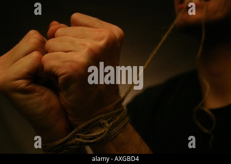 A man tightens a length of twine around his wrists with his own teeth. - Stock Image