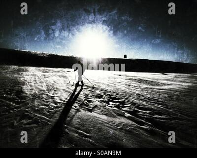 Nordic skier going cross-country skiing into the sun casting a long shadow. - Stock Image