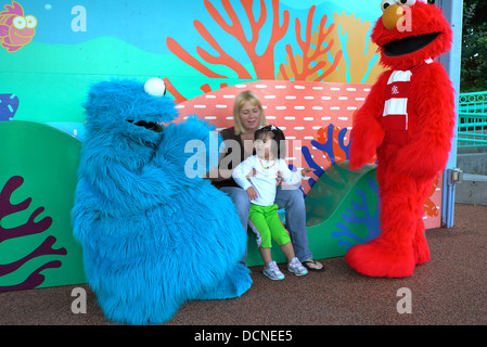 Cookie Monster and Elmo greet young girl at Sea World - Stock Image