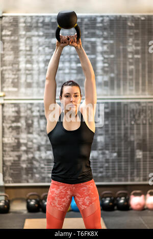 Fit young woman athlete training with a kettlebell raising the weight above shoulder height with extended arms while working out in a gym - Stock Image