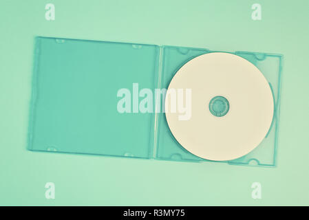 White cd in transparent case on pastel green background - Stock Image