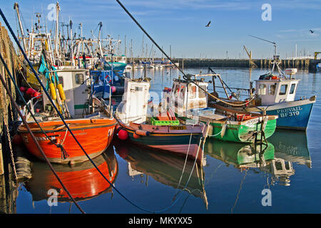 A group of small fishing vessels lit by the evening sun at moorings in Scarborough harbour. - Stock Image
