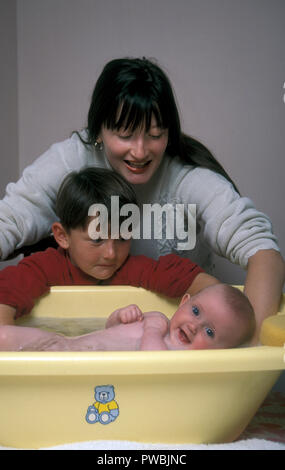 mother showing young son how to bathe newborn baby - Stock Image