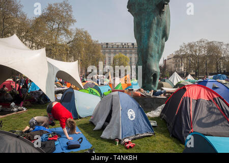 The tents of activists with Extinction Rebellion occupy Marble Arch about climate change beneath the sculpture entitled Horse by Nic Fiddian-Green, on 17th April 2019, in London, England. - Stock Image