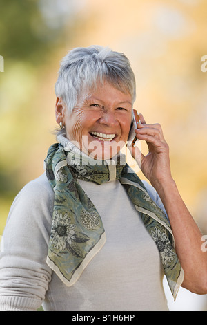 Smiling senior woman using a cell phone - Stock Image