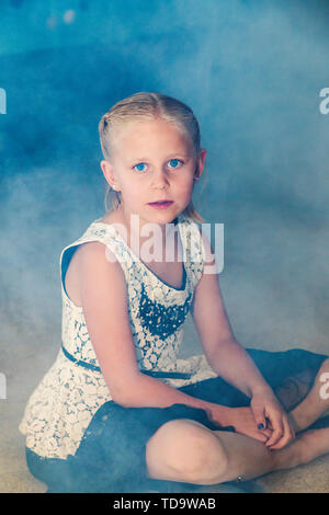 Young girl sitting in artifical fog at wedding reception;  Congressional Church; Buena Vista; Colorado; USA - Stock Image