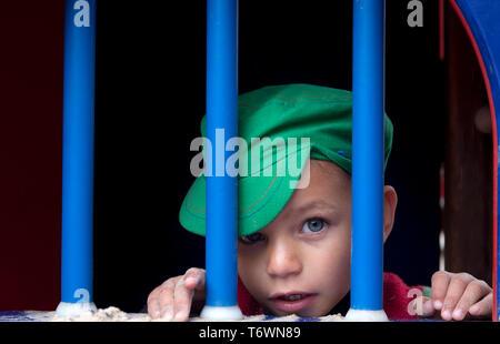 little boy behind bars on playground equipment - Stock Image