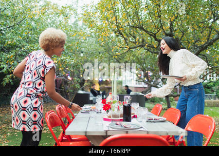 Women friends preparing table for dinner garden party - Stock Image