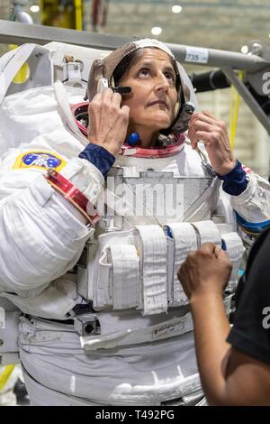Boeing Commercial Crew Program astronaut Suni Williams is assisted with her spacesuit before entering the pool at the Neutral Buoyancy Laboratory for ISS EVA training in preparation for future spacewalks while onboard the International Space Station at the Johnson Space Center April 12, 2019 in Houston, Texas. - Stock Image
