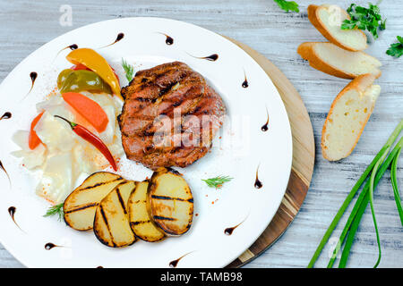 Grilled meat steak with zucchini and pickled vegetables. Cafe menu on a white wooden background with copy space. - Stock Image