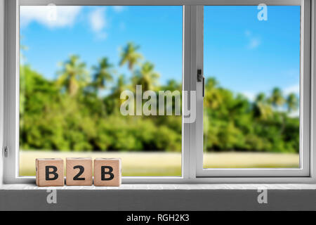 B2B sign in a window on a tropcal island with palm trees under a blue sky - Stock Image