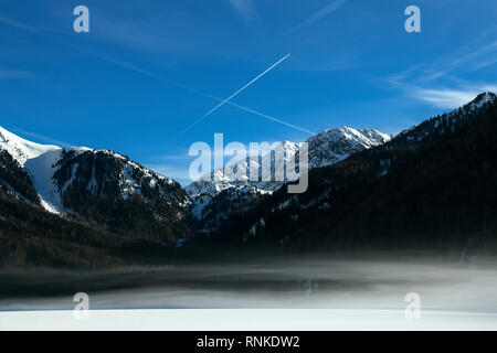 Beautiful mountain landscape with early morning fog on Anterselva - Antholzer See frozen lake in Val Pusteria, South Tyrol -Südtirol, Italian Alps in  - Stock Image
