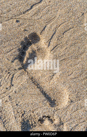 Bare footprint in the wet sand at Fistral Bay, Cornwall. - Stock Image