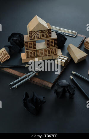 House construction, planning, and repairment concept. Wooden block home on a clipboard with compasses, rulers and pencils. Working on a blueprint - Stock Image