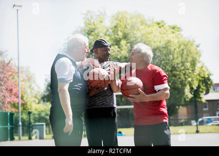 Active senior men friends playing basketball in sunny park - Stock Image