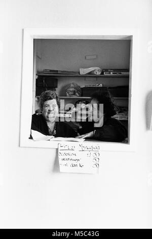 Ladies selling tea & cakes through hatch at small eisteddfod in village hall at Llandudoch St Dogmaels Dyfed - Stock Image