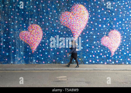 A woman looking at her mobile phone walking past a large painted mural of pink hearts in a street in London. - Stock Image