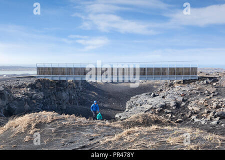 18 April 2018: Sandvik, Iceland - A couple emerging from the gorge at the symbolic Bridge Between Continents in the Reykjanes Peninsula, Iceland, cros - Stock Image
