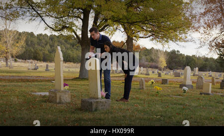 Boyfriend and girlfriend examining grave in lonely cemetery - Stock Image