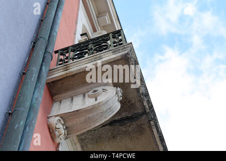 Details of old medieval style building from below. The building has red concrete walls and beautiful balconies. Photographed in Nyon, Switzerland. - Stock Image