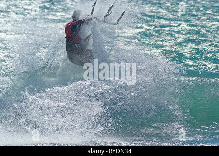 Kite boarder surfing a wave during a windy day at the end of winter in French riviera. (St Laurent du Var spot) - Stock Image