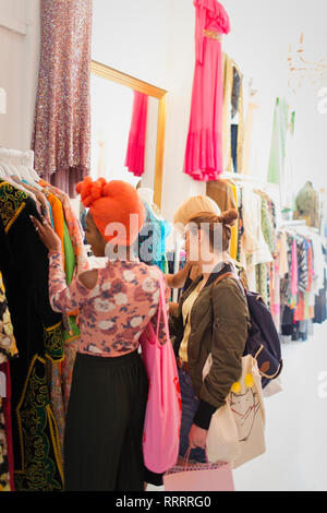 Young women friends shopping in clothing store - Stock Image