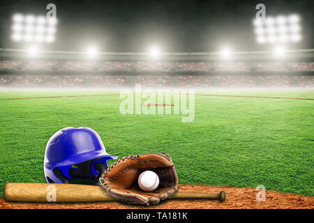 Blue baseball helmet, bat, glove and ball on field at brightly lit outdoor stadium. Focus on foreground and shallow depth of field on background and c - Stock Image