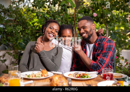 Parents and their daughter sitting at a lunch table - Stock Image