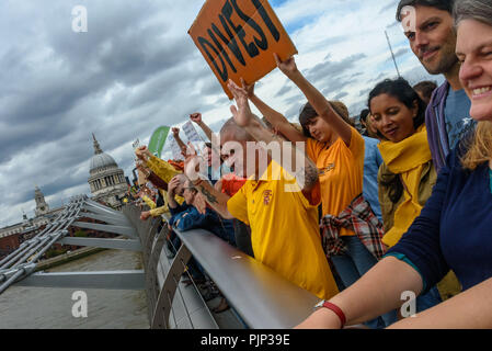 London, UK. 8th September 2018. Climate Reality supporters on the Millennium Bridge for a photo at the end of their rally in front of Tate Modern, one of thousands around the world demanding urgent action by government leaders to leaders commit to a fossil free world that works for all of us.  community leaders, organiser Credit: Peter Marshall/Alamy Live News - Stock Image