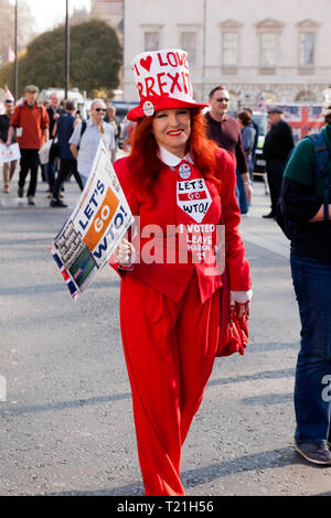 A smiling Lady in  costume  walks by the Houses of Parliament during a  demonstration  against the delays to Brexit  on the day the UK should have left  the EU - Stock Image