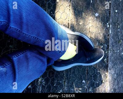 Man wearing jeans and trainers sits with his legs crossed. - Stock Image
