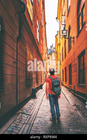 Man traveler walking alone in Stockholm narrow street traveling alone lifestyle summer trip vacations in Sweden - Stock Image