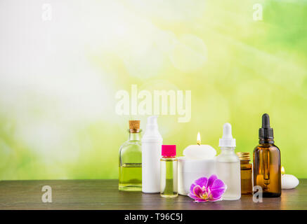 Composition with lot of different size, shape and material beauty cosmetics products bottles arrangement on wooden table with green bokeh studio backg - Stock Image