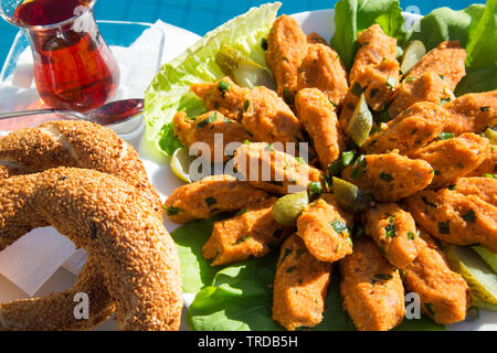 Traditional Turkish afternoon snack of Bulgar wheat and red lentil cigarillos served with Simit bread, Turkish tea and side salad. - Stock Image