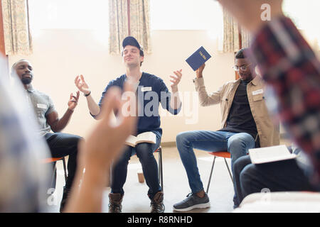 Men with bible praying with arms raised in prayer group - Stock Image