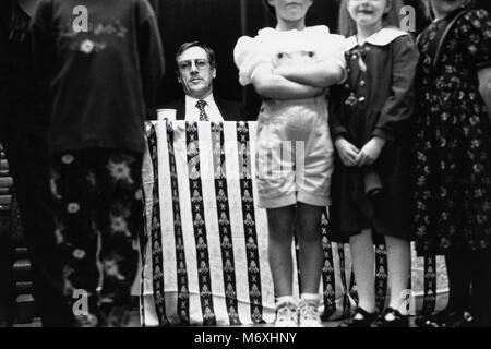 Children lined up on stage with man seated at table behind at small eisteddfod in village hall at Y Groeslon Gwynedd - Stock Image