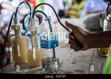 Residents of the flood hit village of Gaung Gyi observe a water purifier donated by an aid agency. Myanmar - Stock Image