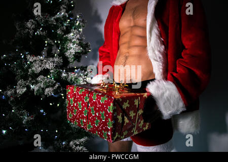 Sexy male santa with open jacket revealing six pack abs and fit body, wearing shorts, carrying a gift with christmas tree in background - Stock Image