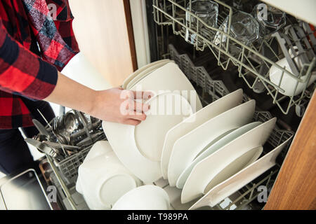 Woman takes out clean dishes from the dishwasher. - Stock Image