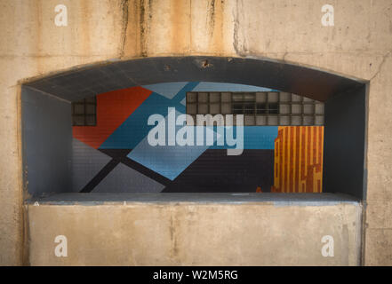 A wall painted with colorful blue patterns can be seen through an archway opening in a cement wall - Stock Image