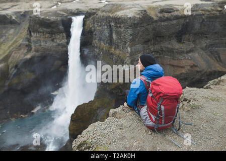 Hiker with backpack on cliff by Haifoss waterfall in Iceland - Stock Image