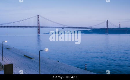 Landmark 25 of April bridge on Tagus River with Cristo Rei in background, Lisbon, Portugal. - Stock Image