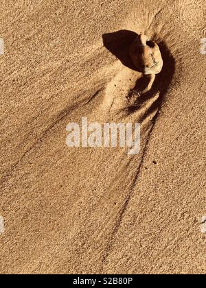 A stone lying on sand has created a pattern as the tide recedes. - Stock Image