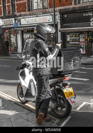 A stationary motorbike rider taking a break and checking a mobile phone, while standing by the side of the road, - Stock Image