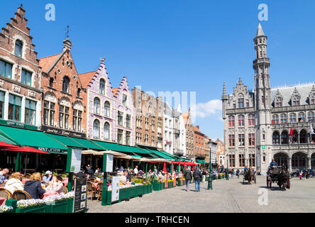Bruges Tourists in a horse drawn carriage going past the cafes near the Provincial Court Provinciaal Hof in the Markt central Bruges Belgium EU Europe - Stock Image