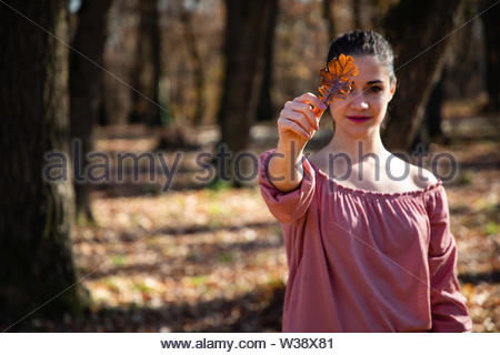 Beautiful girl holding a brown leaf covering her eye - Stock Image