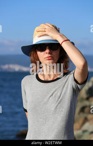 Young Beautiful Woman In Straw Hat And Looking At Camera On The Beach. Close Up Portrait - Stock Image