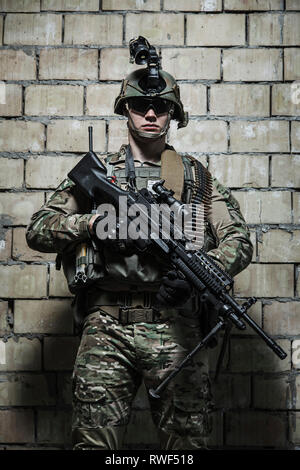 U.S. Army Ranger with machine gun and night vision goggles standing near a wall. - Stock Image
