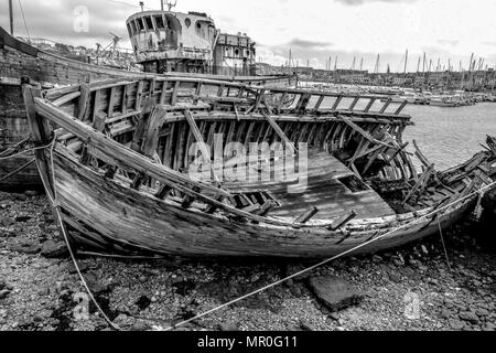 Crumbling ships in the boat graveyard at Camaret-sur-Mer in the Finistere region of Brittany, France. Black and white. B&W - Stock Image
