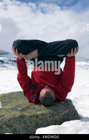 Adult male performing an Urdhva Padmasana yoga, upside down lotus on frozen Finse Vatn lake, Finse, Norway - Stock Image